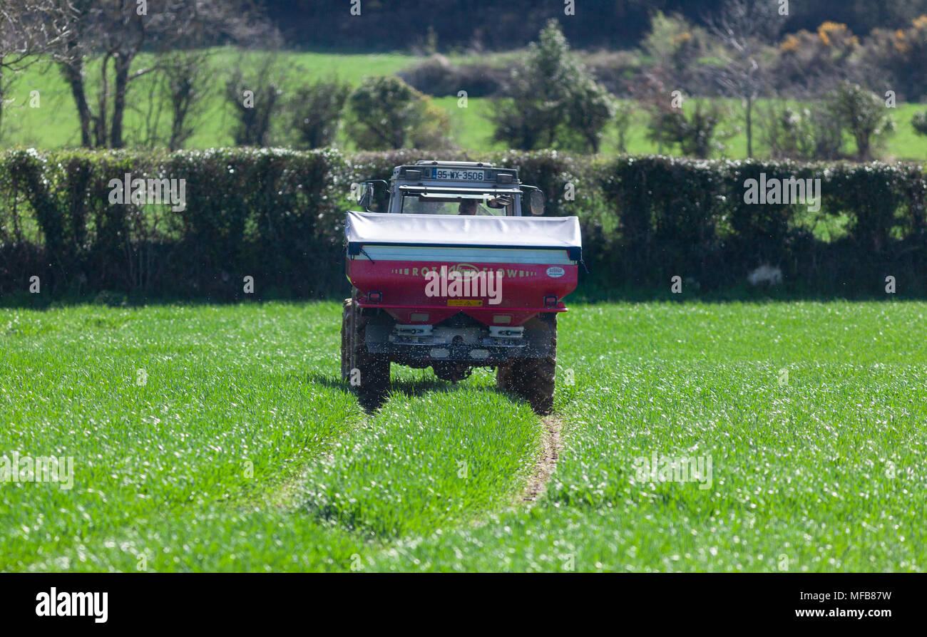 Tractor spreading fertilizer on field Stock Photo