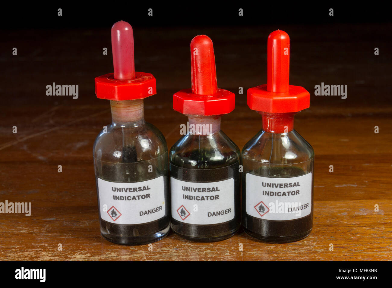 Three dropping bottles of Universal indicator liquid as used in a UK secondary/high school. - Stock Image