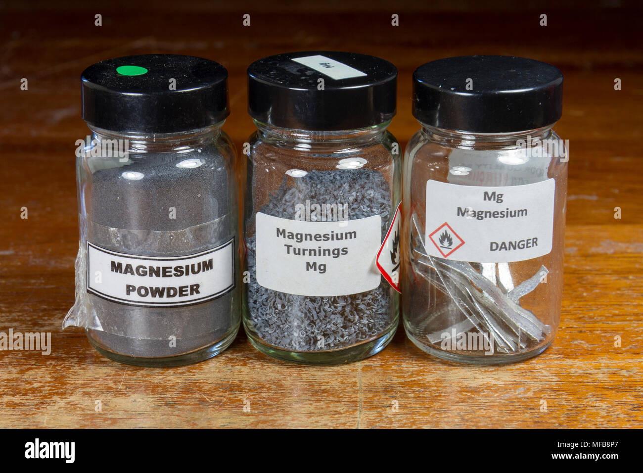 Jars containing Magnesium metal in three different forms (powder, turnings and strips)as used in a UK secondary/high school. - Stock Image