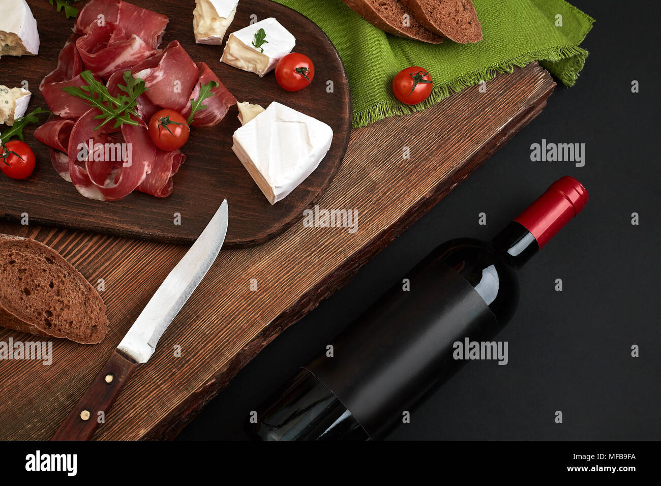 Wine bottle with cheese and traditional sausages on wooden board on black background with copy space - Stock Image