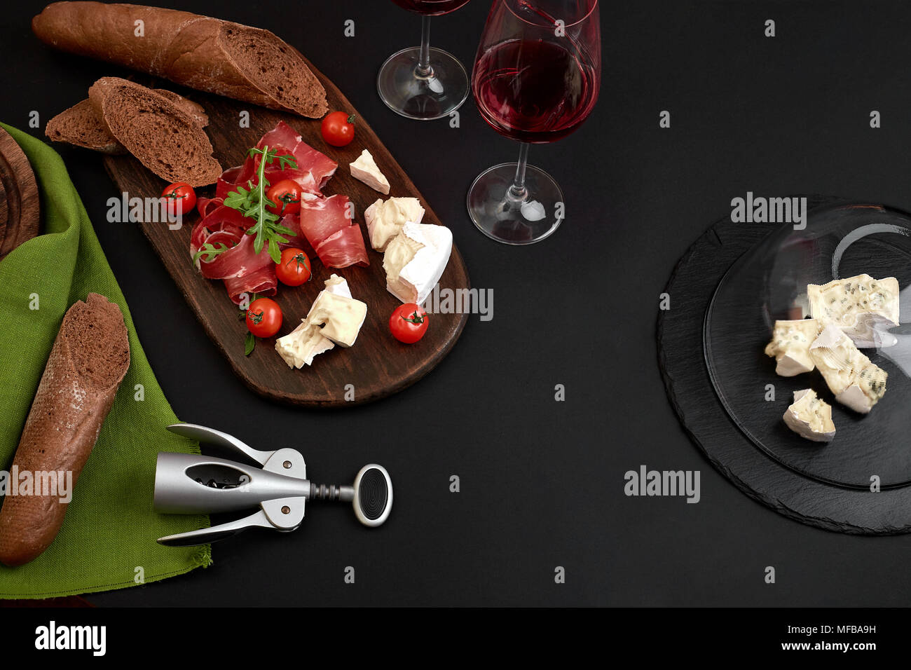 Prosciutto, salami, baguette slices, tomatoes and nutson rustic wooden board, two glasses of red wine over black background Stock Photo