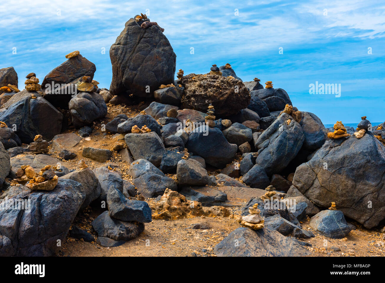 Large rocks topped with mementos lead to a hilltop on a beach in Aruba. - Stock Image