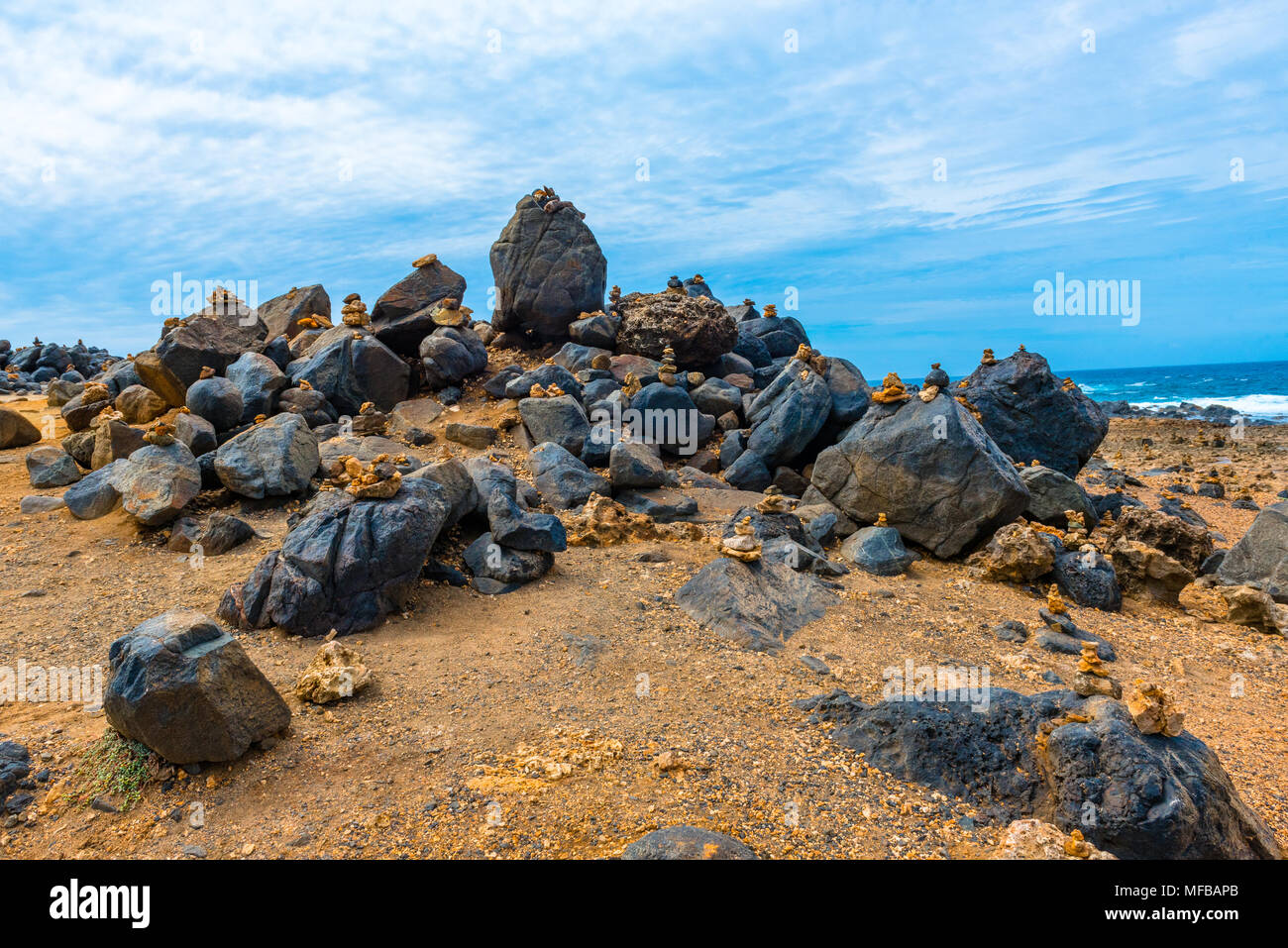 Large rocks topped with mementos cover a beach in Aruba. - Stock Image