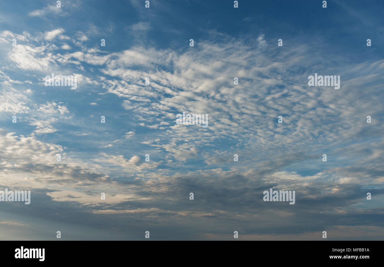 Moving clouds with a blue sky ,ideal for a backdrop,texture overlay or replacement sky in Photoshop. - Stock Image