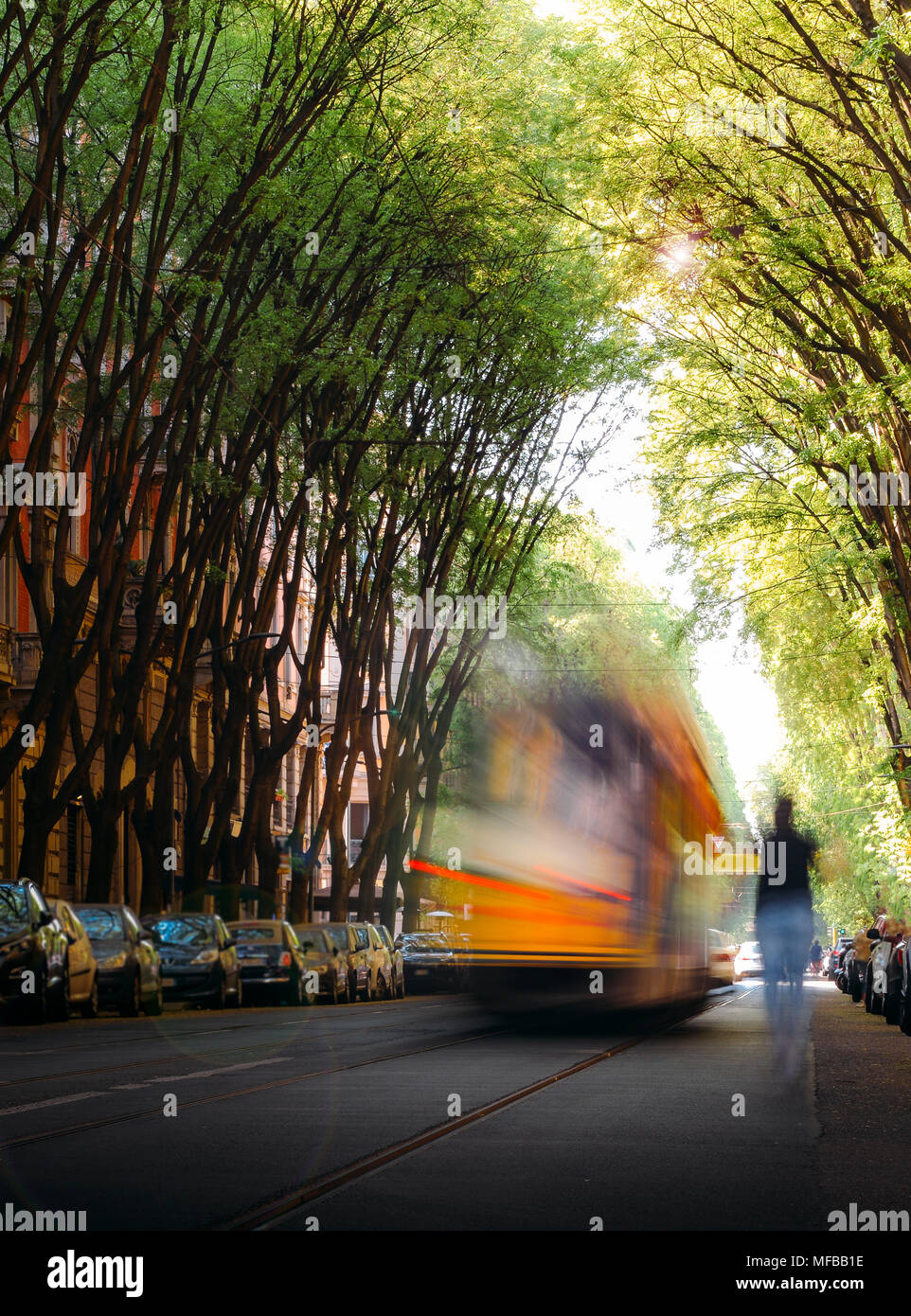 Unidentifiable person running towards an out of blur tram on a tree-lined path on the street - stressful situation in urban setting - Stock Image