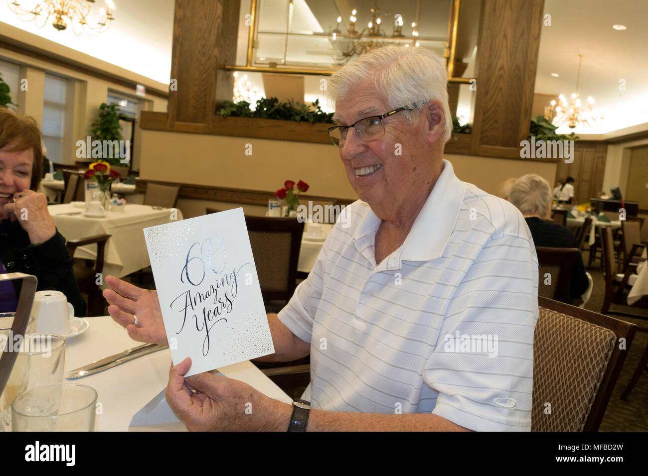 Happy husband of sixty years of marriage reading a greeting card during a restaurant celebration. Downers Grove Illinois IL USA - Stock Image