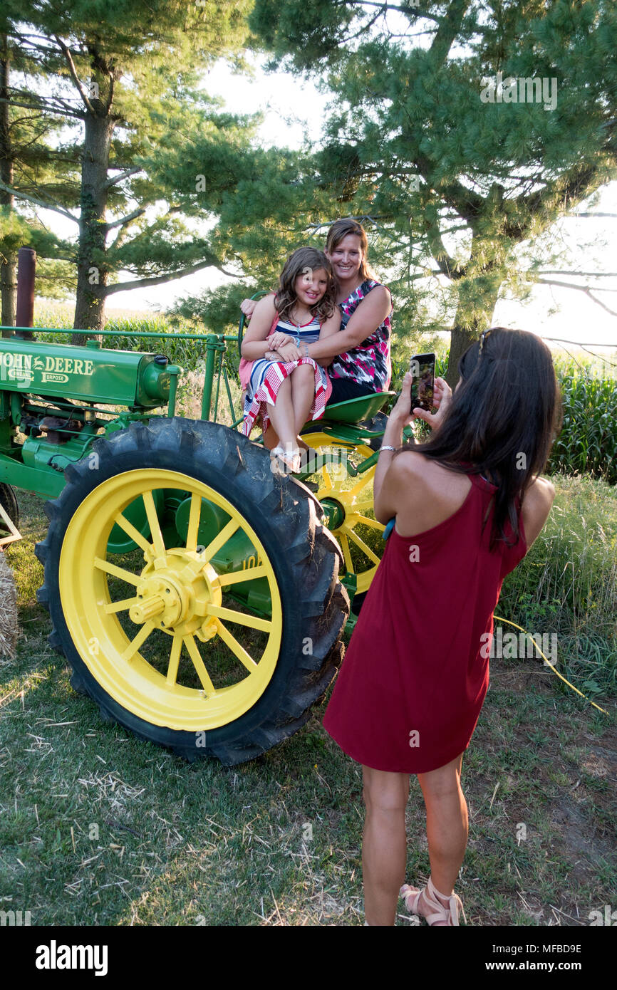 Mom and daughter being photographed on a John Deere antique tractor during the reception of a family wedding. Champaign Illinois IL USA - Stock Image
