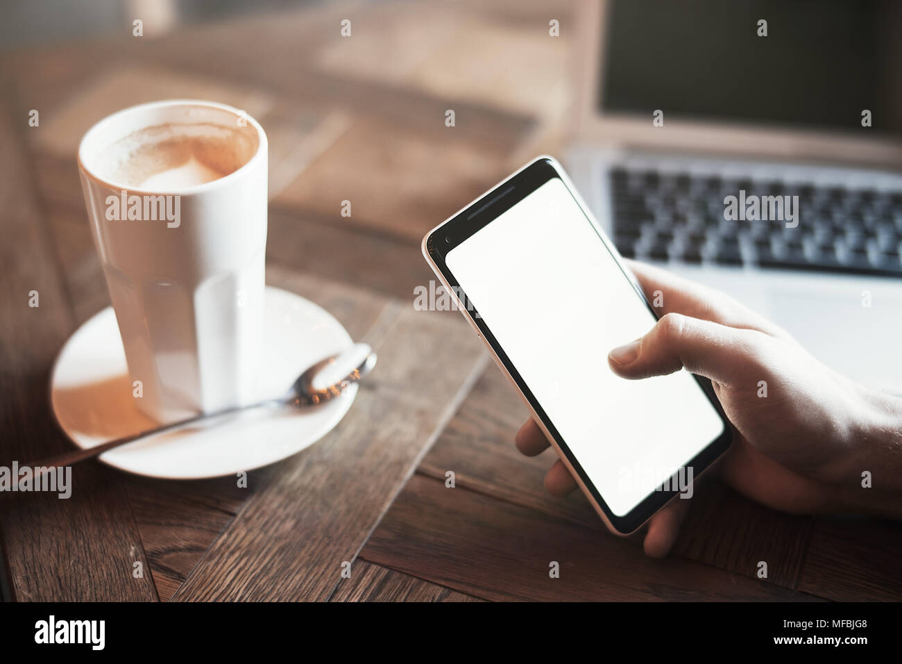 Young man with tattoo holding mobile phone and working on laptop in co-working. Mans hand and phone are on foreground and on focus. - Stock Image