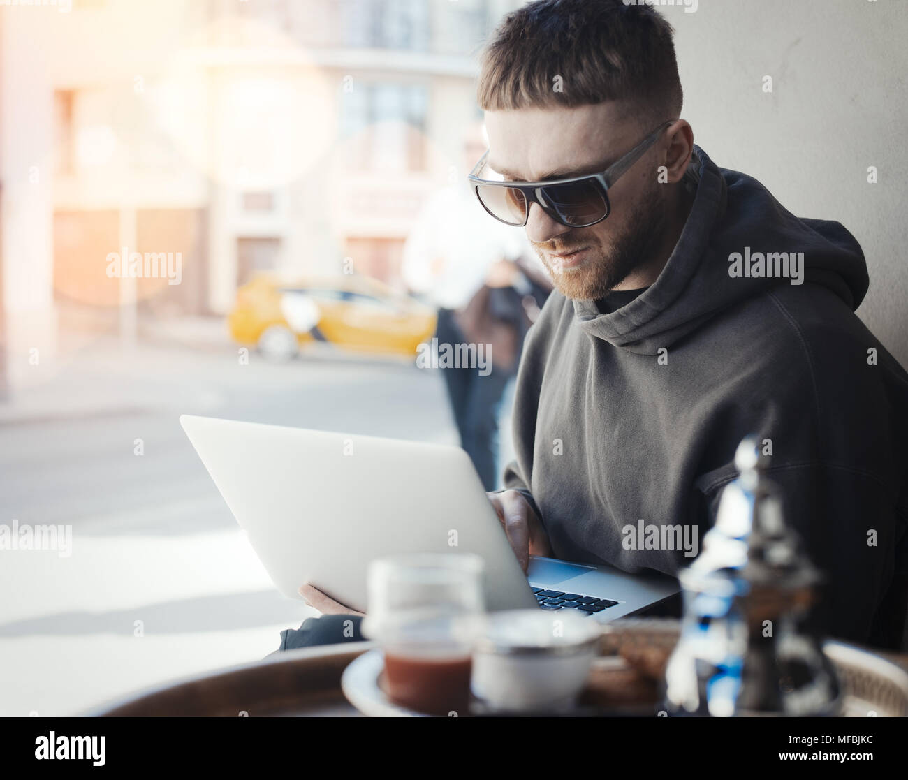 Pensive young man holding laptop on his knees and working on it in cafe. PC and man are on focus and background. Cutlery and tea are on foreground - Stock Image