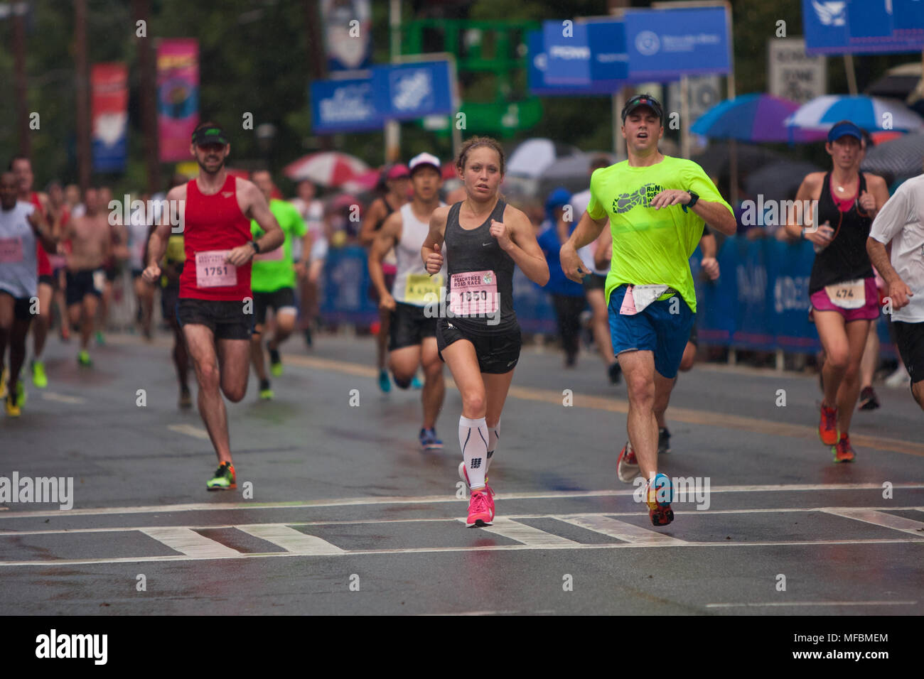 Atlanta, GA, USA - July 4, 2015:  Exhausted runners cross the finish line in the rain at the 46th annual Peachtree Road Race 10K in Atlanta. - Stock Image