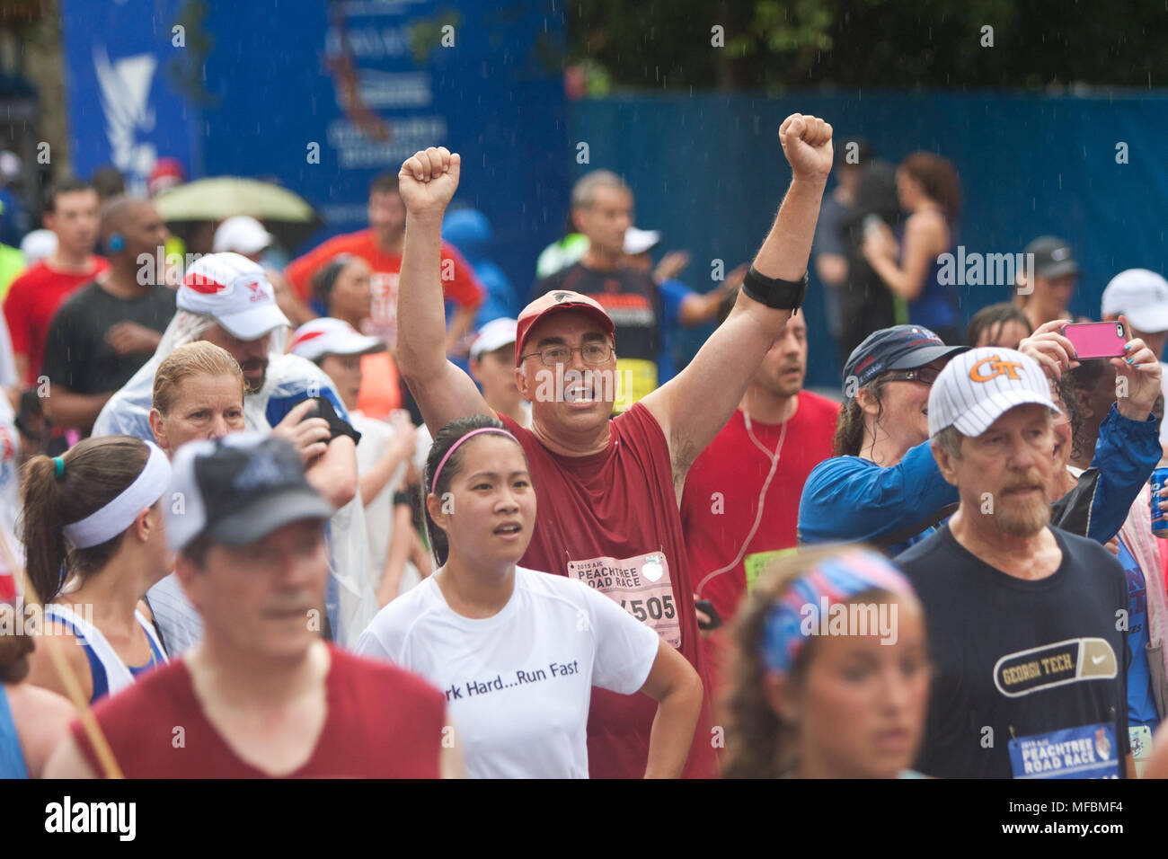 A man raises his arms triumphantly among a crowd of runners crossing the finish line at the Peachtree Road Race on July 4, 2015 in Atlanta, GA. - Stock Image