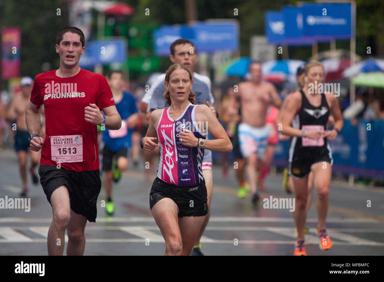 Tired runners push for the finish line in the rain, at the 46th running of the Peachtree Road Race 10K on July 4, 2015 in Atlanta, GA. - Stock Image