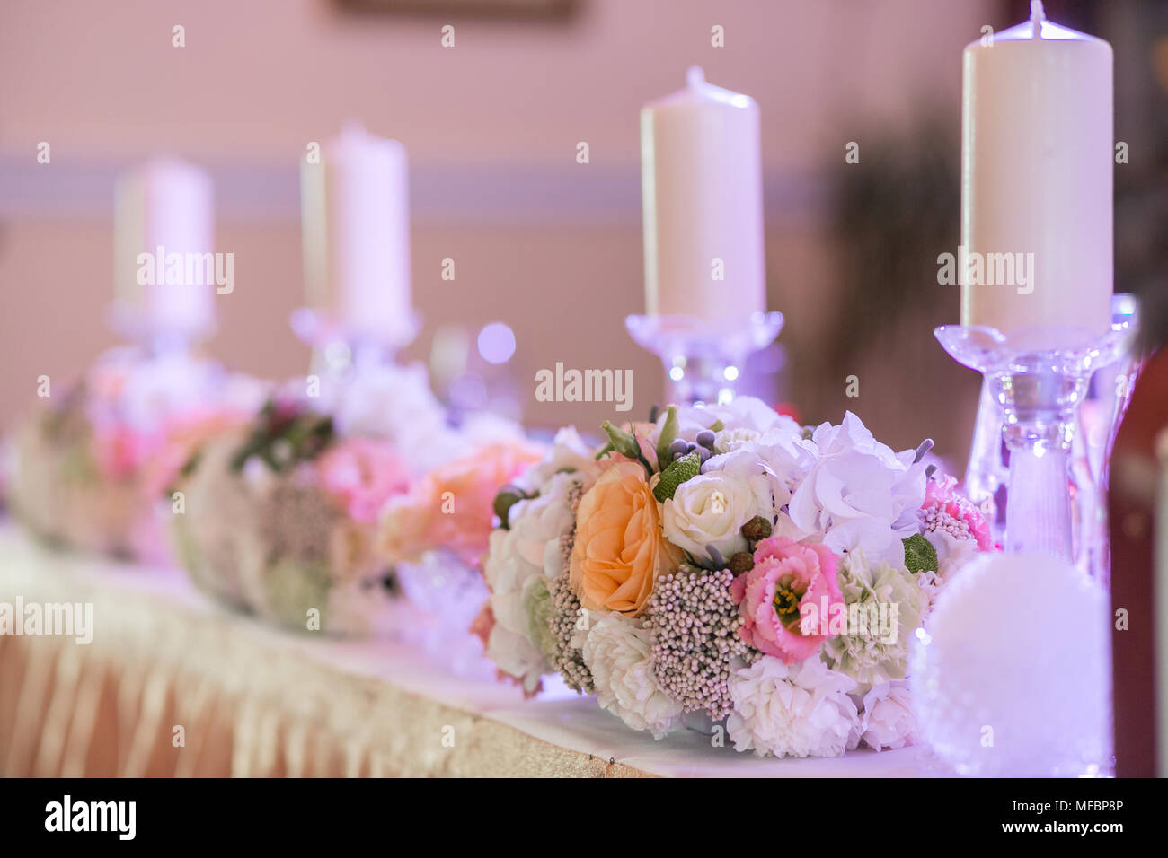 White candles on metal gold candlesticks stand on tables at luxury wedding reception in restaurant. Stock Photo