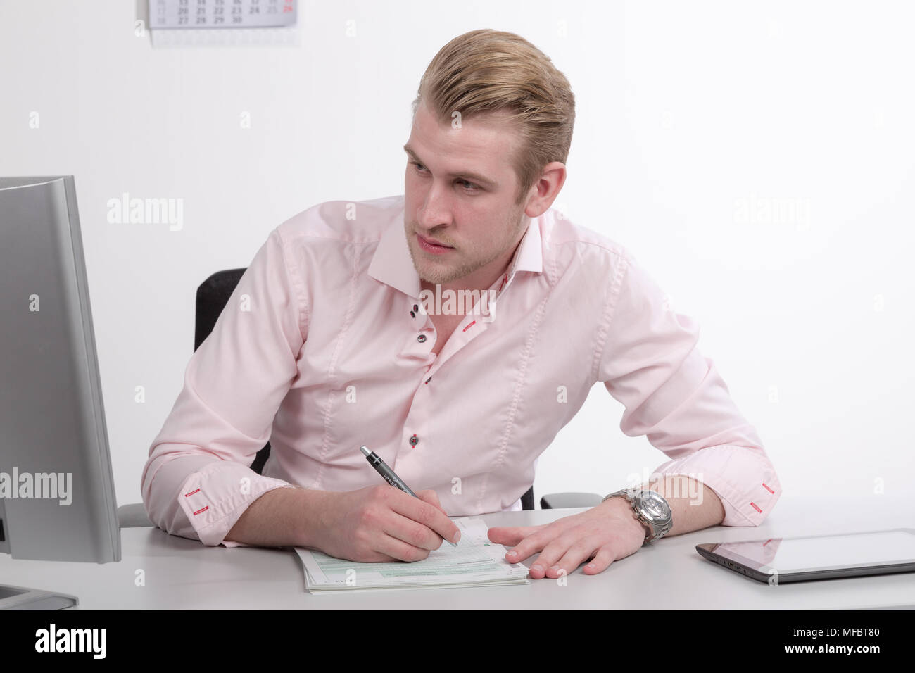 Young man working at desk on paper work - Stock Image