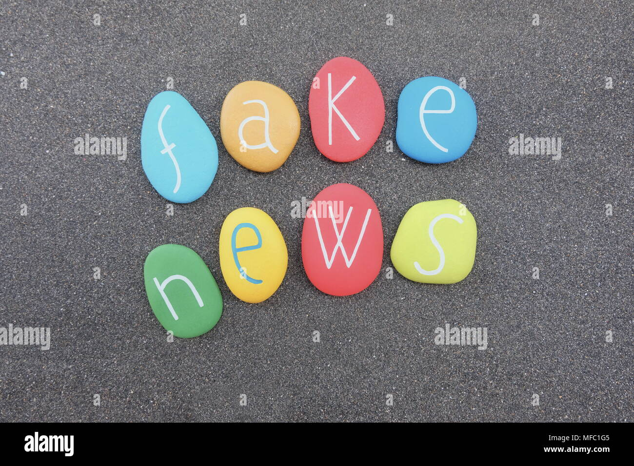 Fake news text with multicolored stones over black volcanic sand Stock Photo