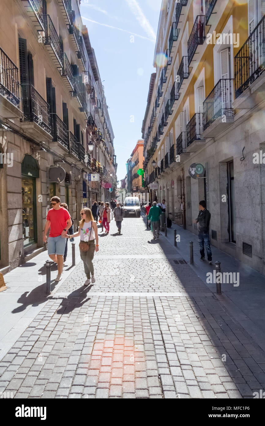 Madrid, Spain - March 9, 2015: On a sunny winter day, shoppers peruse store windows in central Madrid. - Stock Image