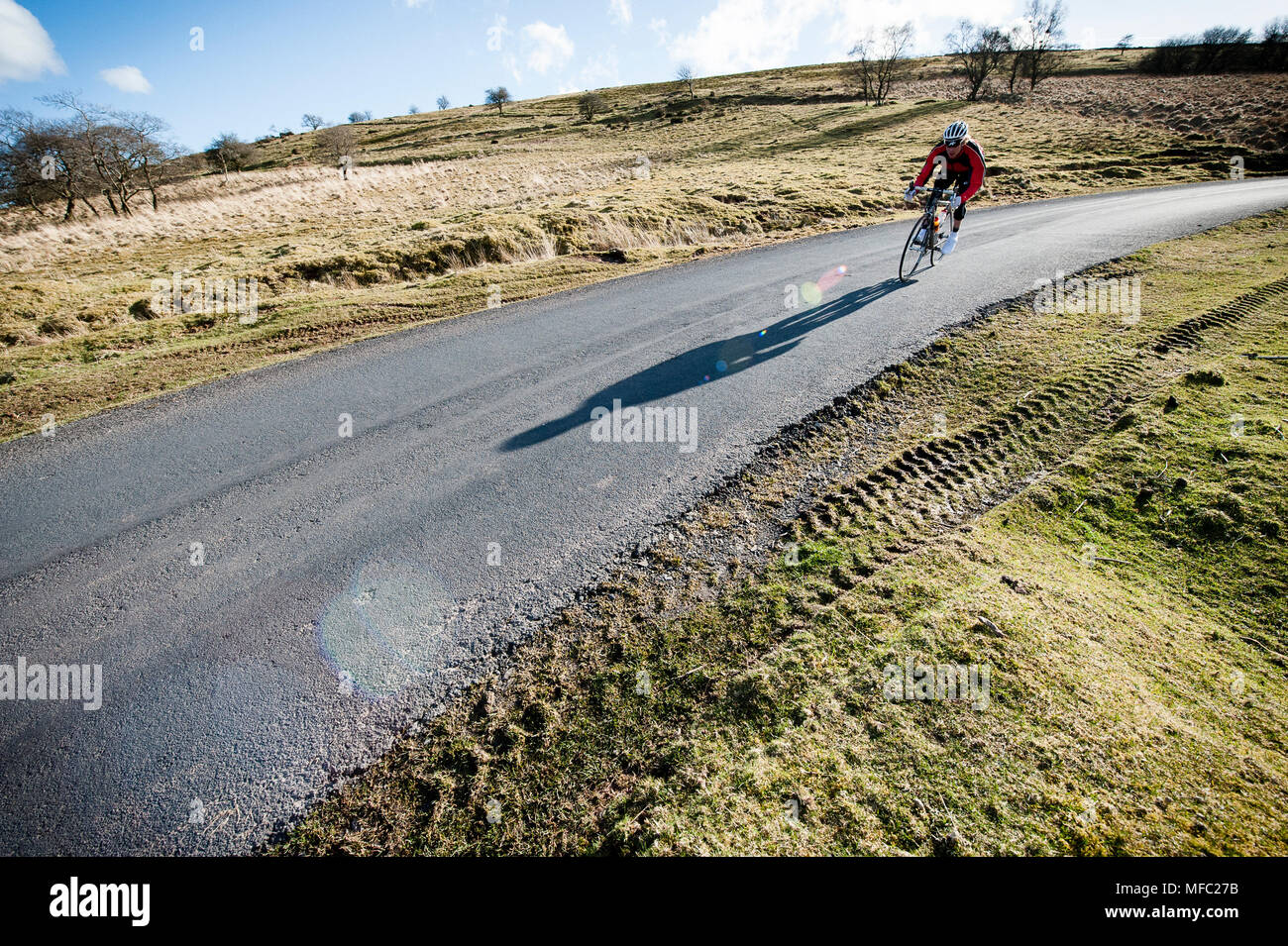 Solo Cyclist riding on a Road in the Brecon Beacon in Wales Stock Photo