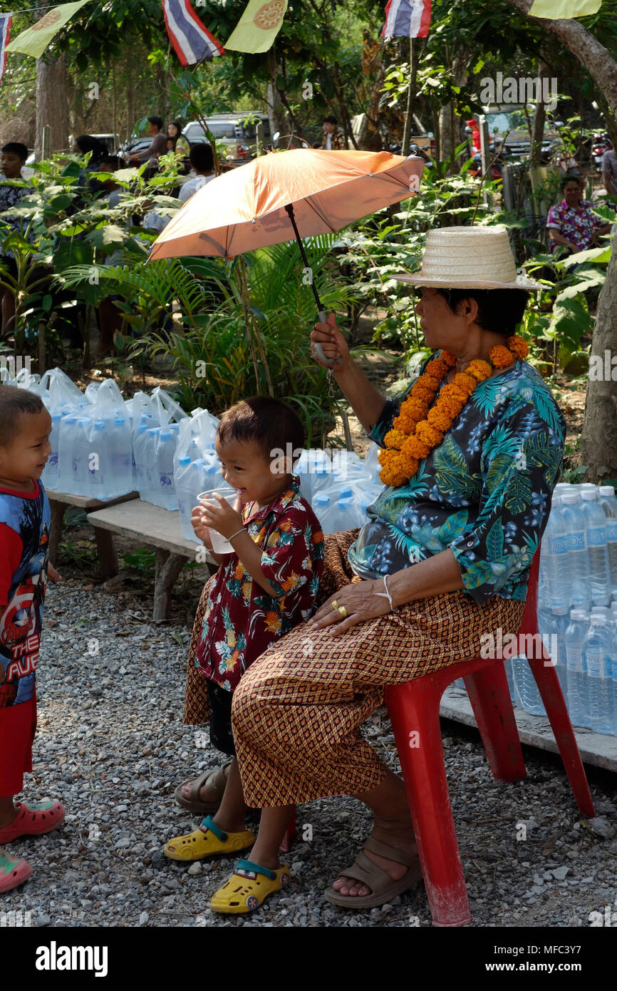 Thai grandmother in celebratory clothing and and two children seated with  umbrella in temple grounds on
