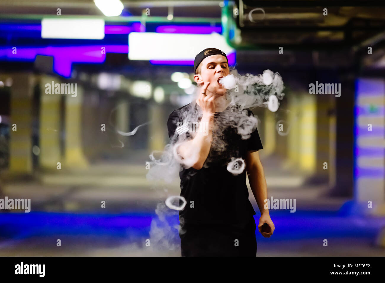 Man in cap smoke an electronic cigarette and releases clouds of vapor performing various kind of vaping tricks - Stock Image