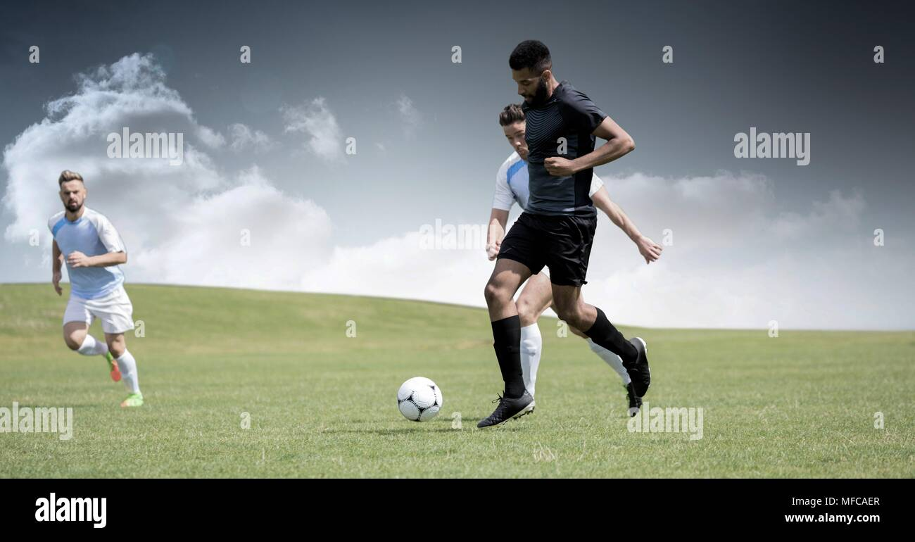 Soccer players on grass with sky - Stock Image