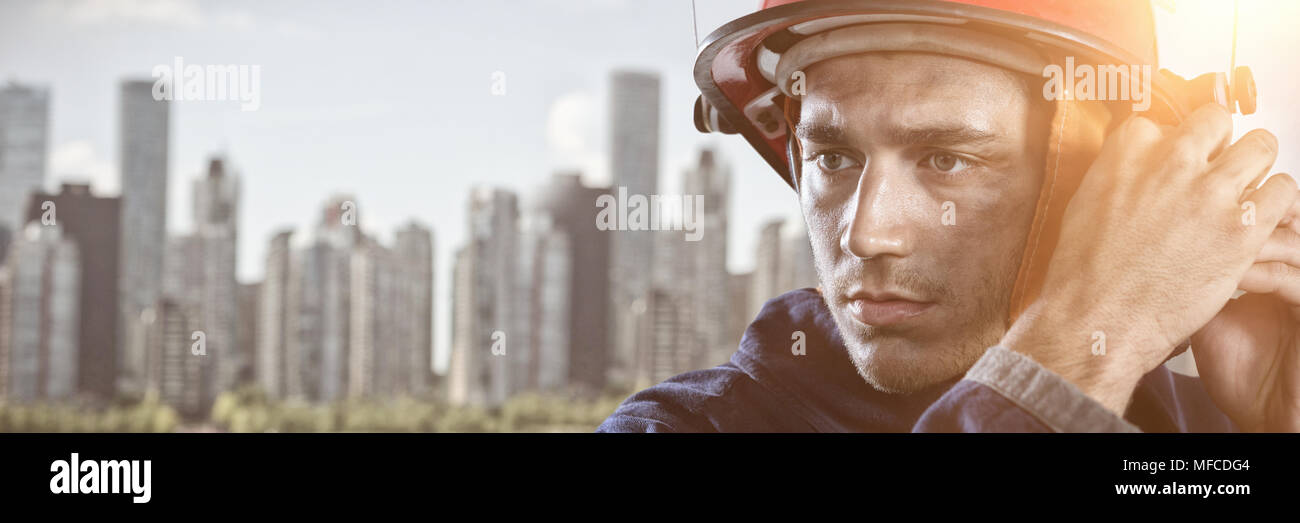 Composite image of serious fireman putting on helmet - Stock Image