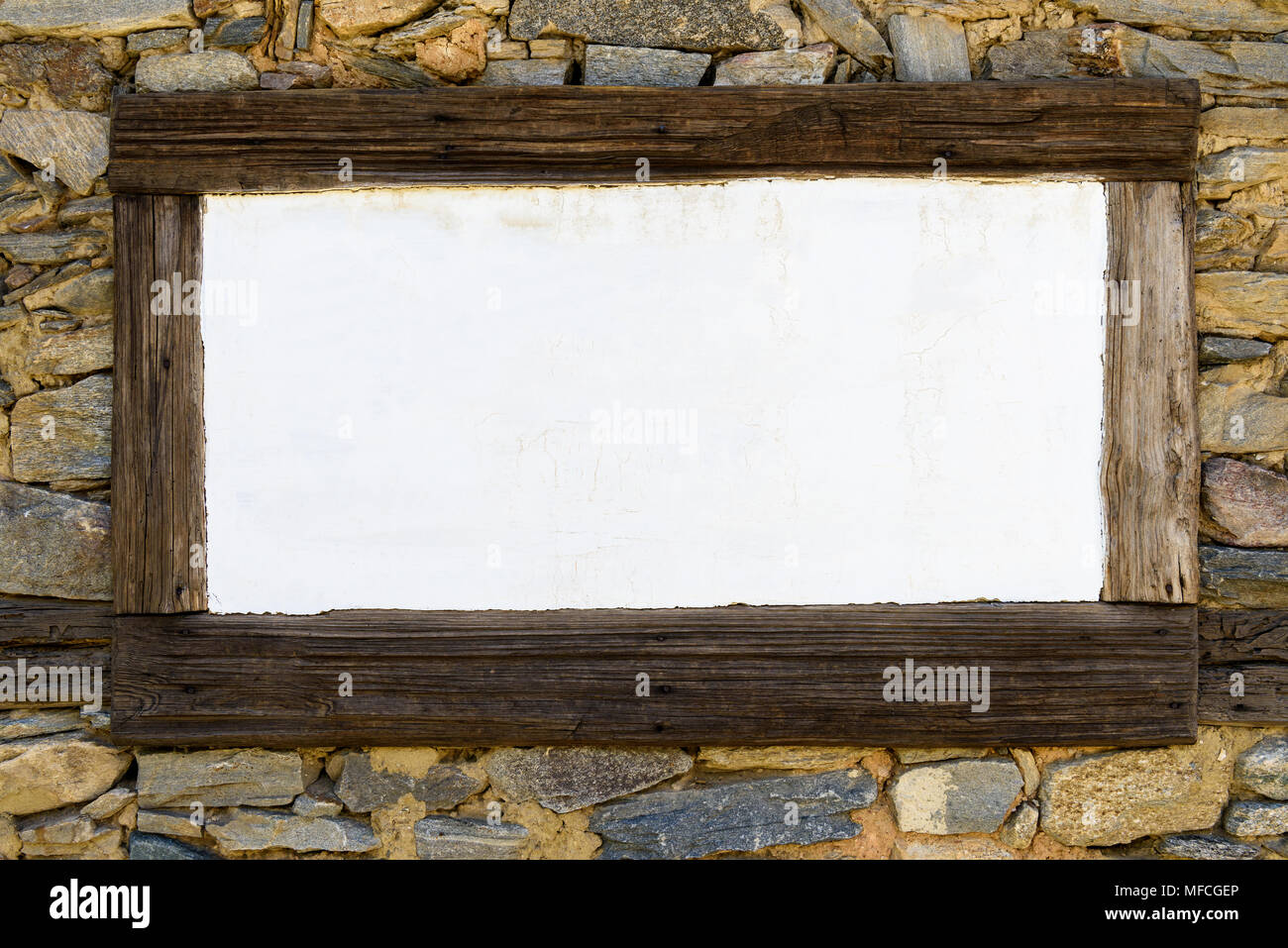 Blank white chalkboard in wooden frame on stone wall Stock Photo ...