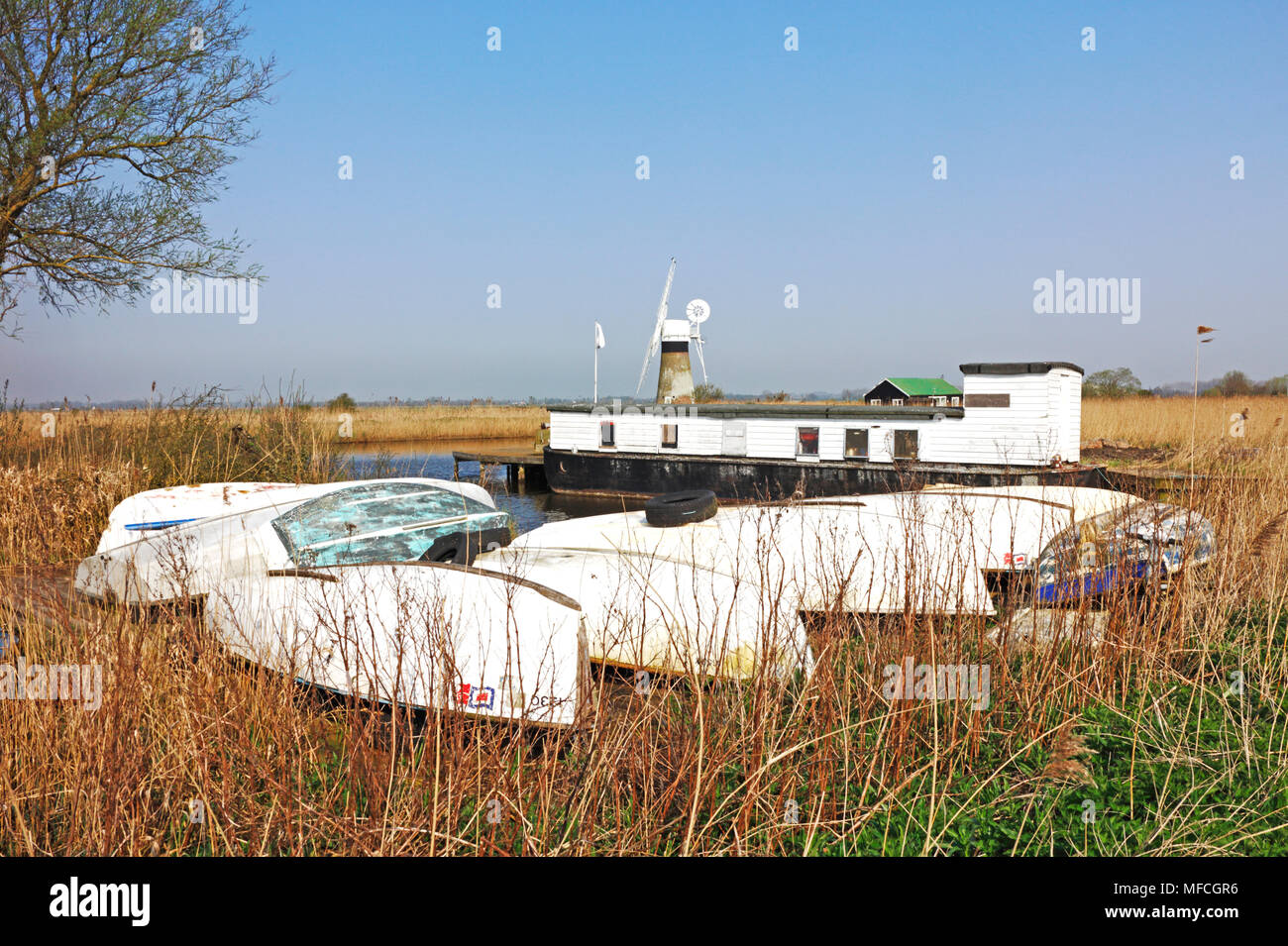 A group of upturned dinghies by the River Thurne on the Norfolk Broads at Thurne, Norfolk, England, United Kingdom, Europe. - Stock Image