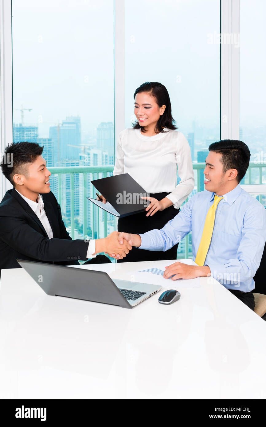 Asian banker counseling man in office - Stock Image