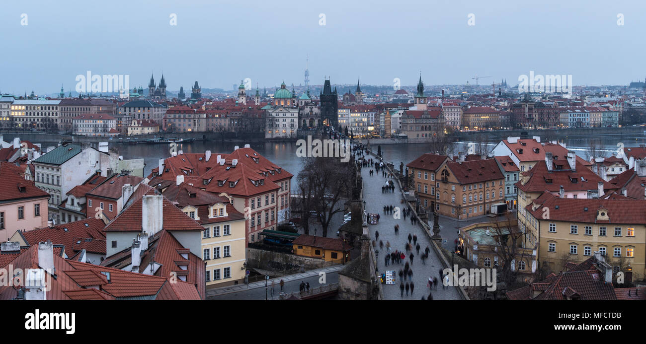 High angle panorama of the famous Charles Bridge and the old town tower and churches in Prague, Czech Republic capital city at nightfall - Stock Image