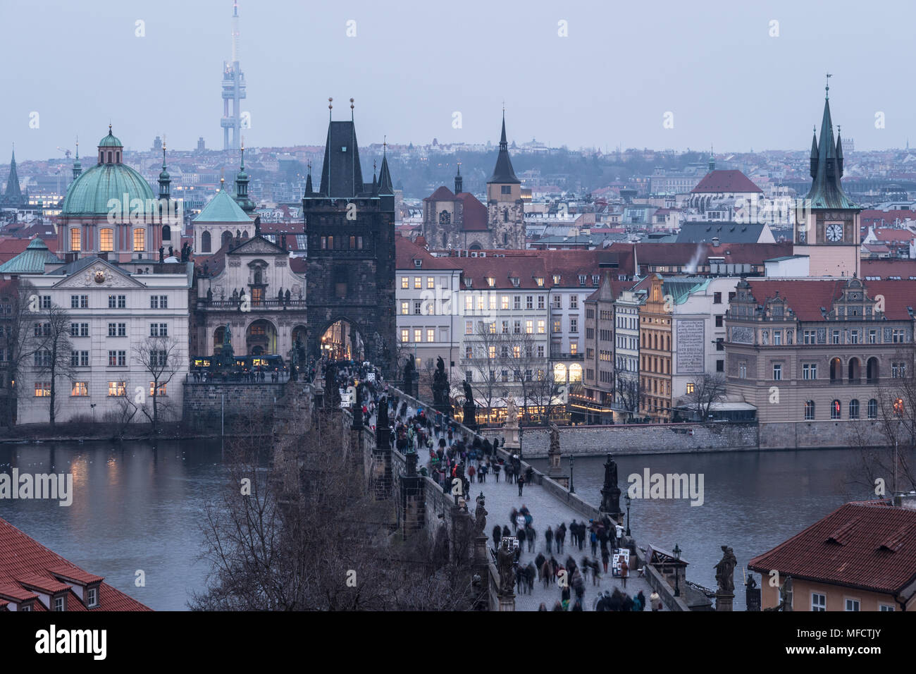 High angle view of the famous Charles Bridge and the old town tower and churches in Prague, Czech Republic capital city at nightfall - Stock Image