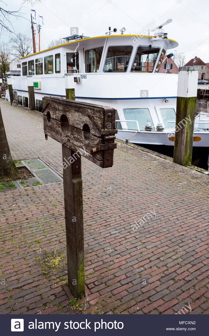 An antique punitive stock stands in the harbor area of the small city of Elburg, in the Netherlands, Rederij Randmeer in background. - Stock Image