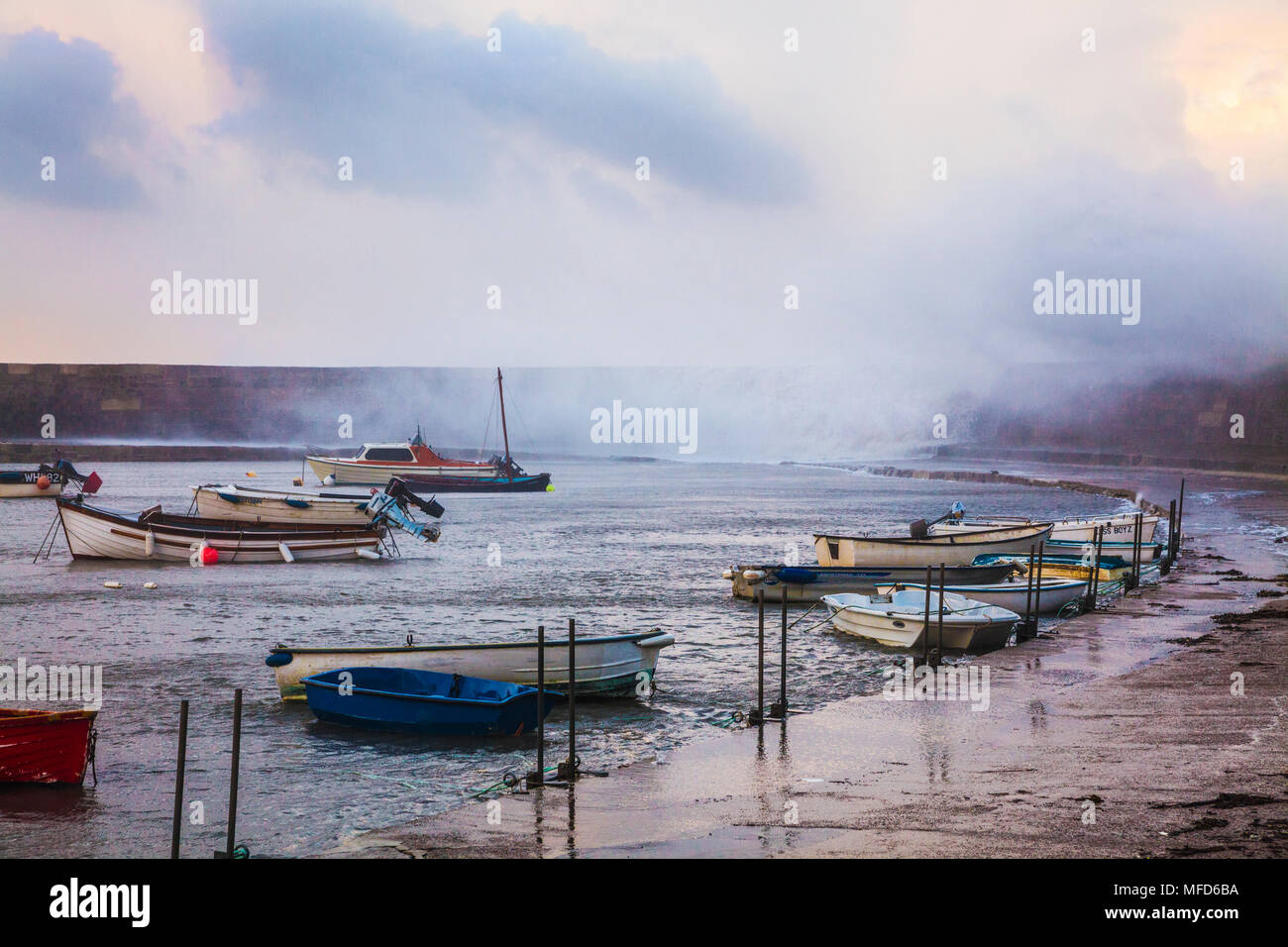 Waves crash over the Cobb at Lyme Regis in Dorset during Storm Brian on Saturday 21st October 2017. - Stock Image