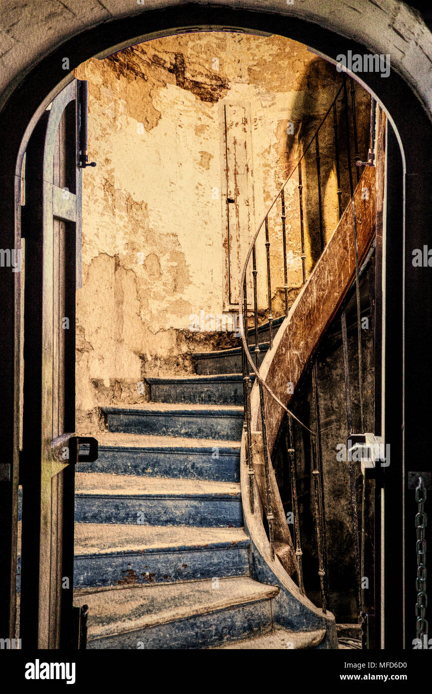 A composite image showing the view through a doorway to a mysterious shadow descending a derelict staircase. - Stock Image
