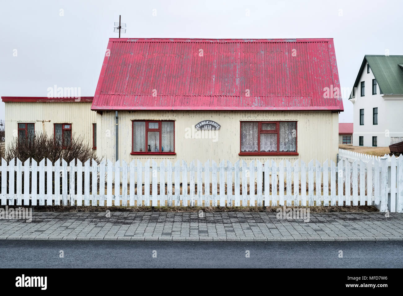 Eyrarbakki, South Iceland. Typical old 19c corrugated-iron cottage with white picket fence, with a sign dating it to 1870 - Stock Image