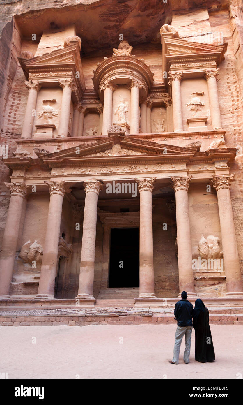 Arab couple looking at the temple carved in the rock of El Hazne, the capital of the Nabataean kingdom, Petra, Jordan - Stock Image