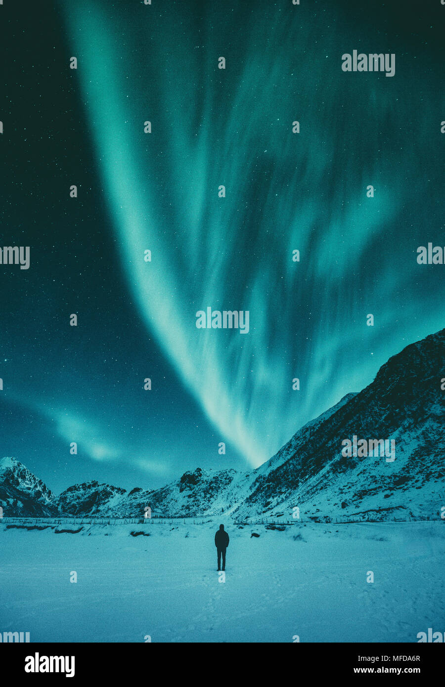 Young man is standing on a remote beach watching the Northern Lights dance above mountains in winter, Lofoten Islands archipelago, Norway, Scandinavia Stock Photo
