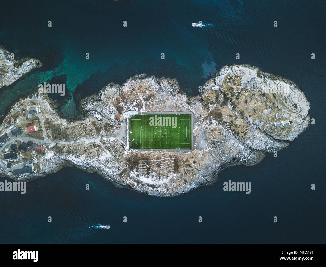 Aerial view of Henningsvaer football stadium with fisherman boats on the Atlantic Ocean, Lofoten Islands archipelago, Norway, Scandinavia - Stock Image