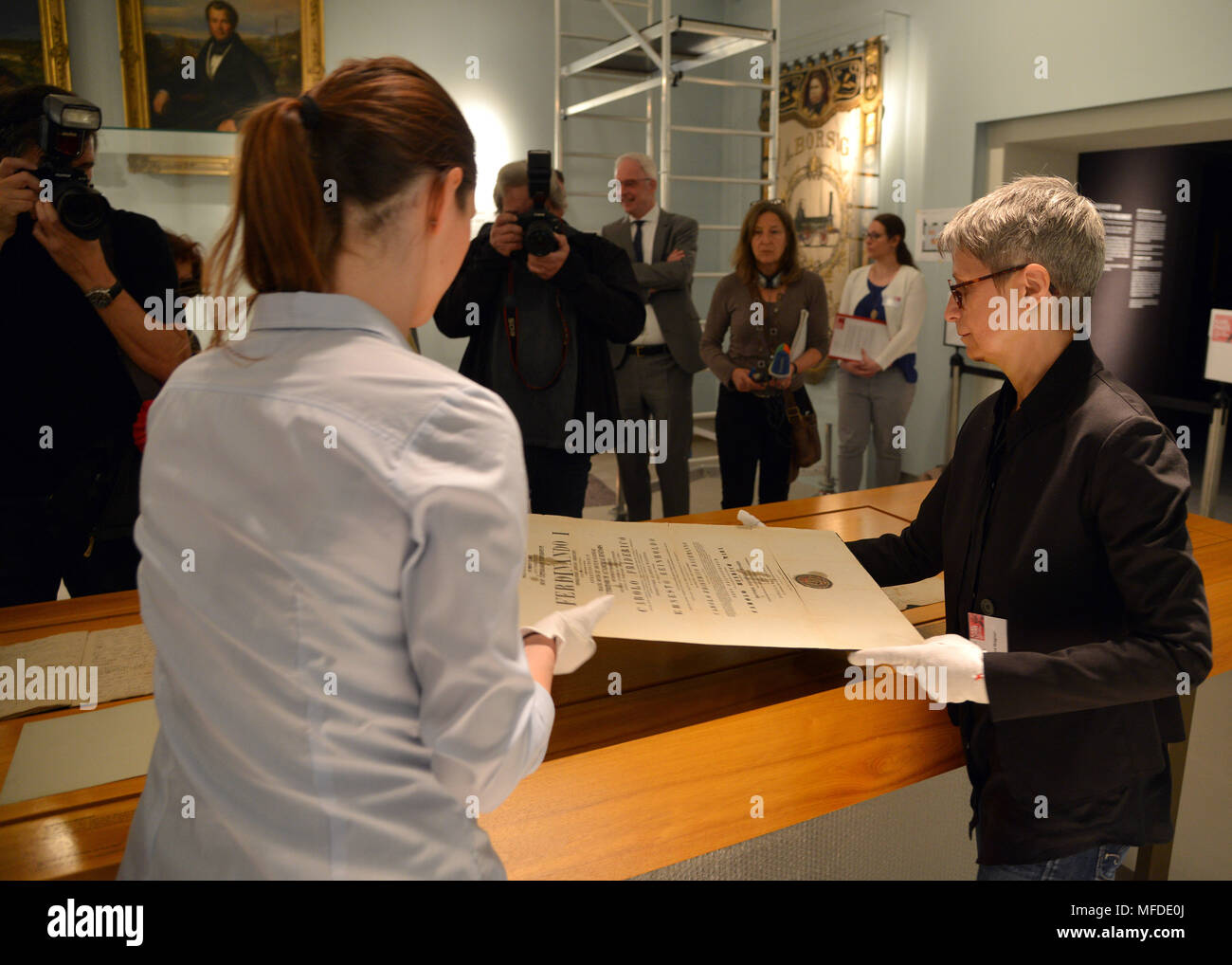 "25 April 2018, Germany, Trier: Curator Barbara Wagner (R) and restorator Sarah Bruch place the doctoral certificate of Karl Marx on the exhibition table at the large Karl Marx exhibition at the Rheinische Landesmuseum Trier. According to its organizers, Rhineland-Palatinate's state exhibition ""Karl Marx 1818 - 1883. Life. Work. Times"" is the first ever historico-cultural exhibition on the thinker. It can be seen at the Rheinische Landesmuseum Trier and at the Simeonstift Trier city museum. Photo: Harald Tittel/dpa Stock Photo"