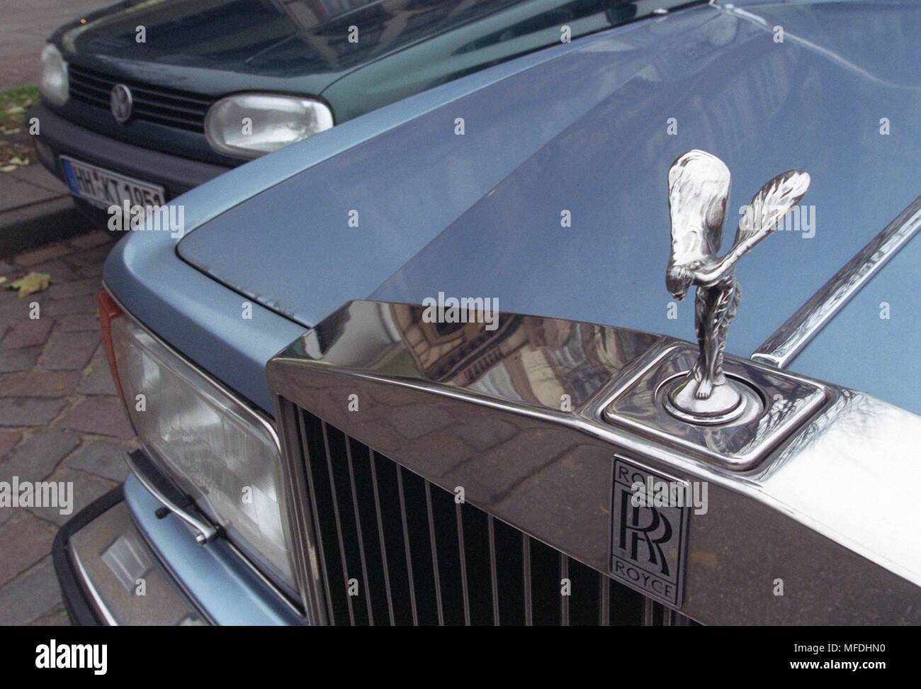 The Pristine Kuhler Hood Of A Rolls Royce R Next To A Golf Of The
