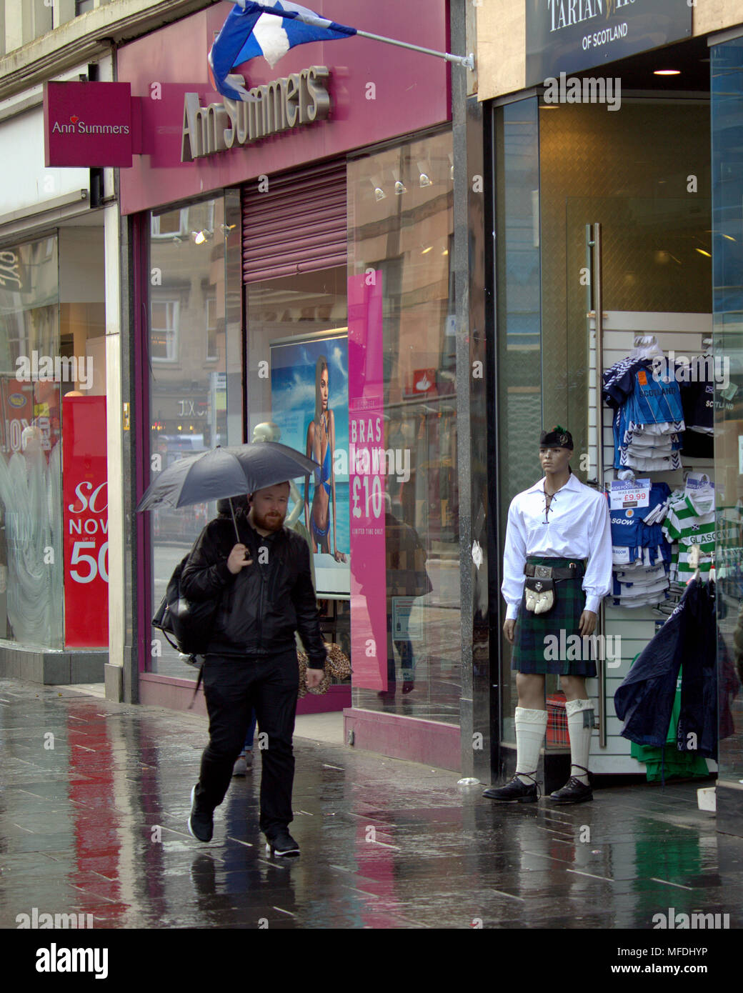 Glasgow, Scotland, UK 25th April. UK Weather:man with umbrella brolly in rain walks past kilt Scottish manikin dummy with Ann summers sign summer parody Sunshine and showers wet pavements street shopping as the locals and tourists enjoy the beginning of summer. Gerard Ferry/Alamy news - Stock Image