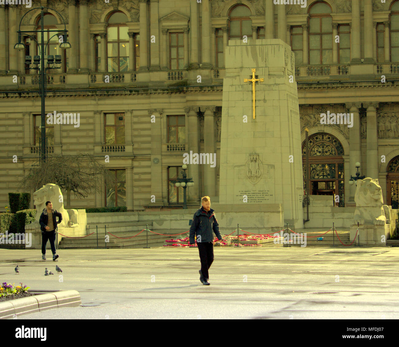 Glasgow, Scotland, UK 25th April. UK Weather:young man walks past the cenotaph and city chambers in sunshine George Square locals and tourists inn  Sunshine and showers as the locals and tourists enjoy the beginning of summer. Gerard Ferry/Alamy news - Stock Image