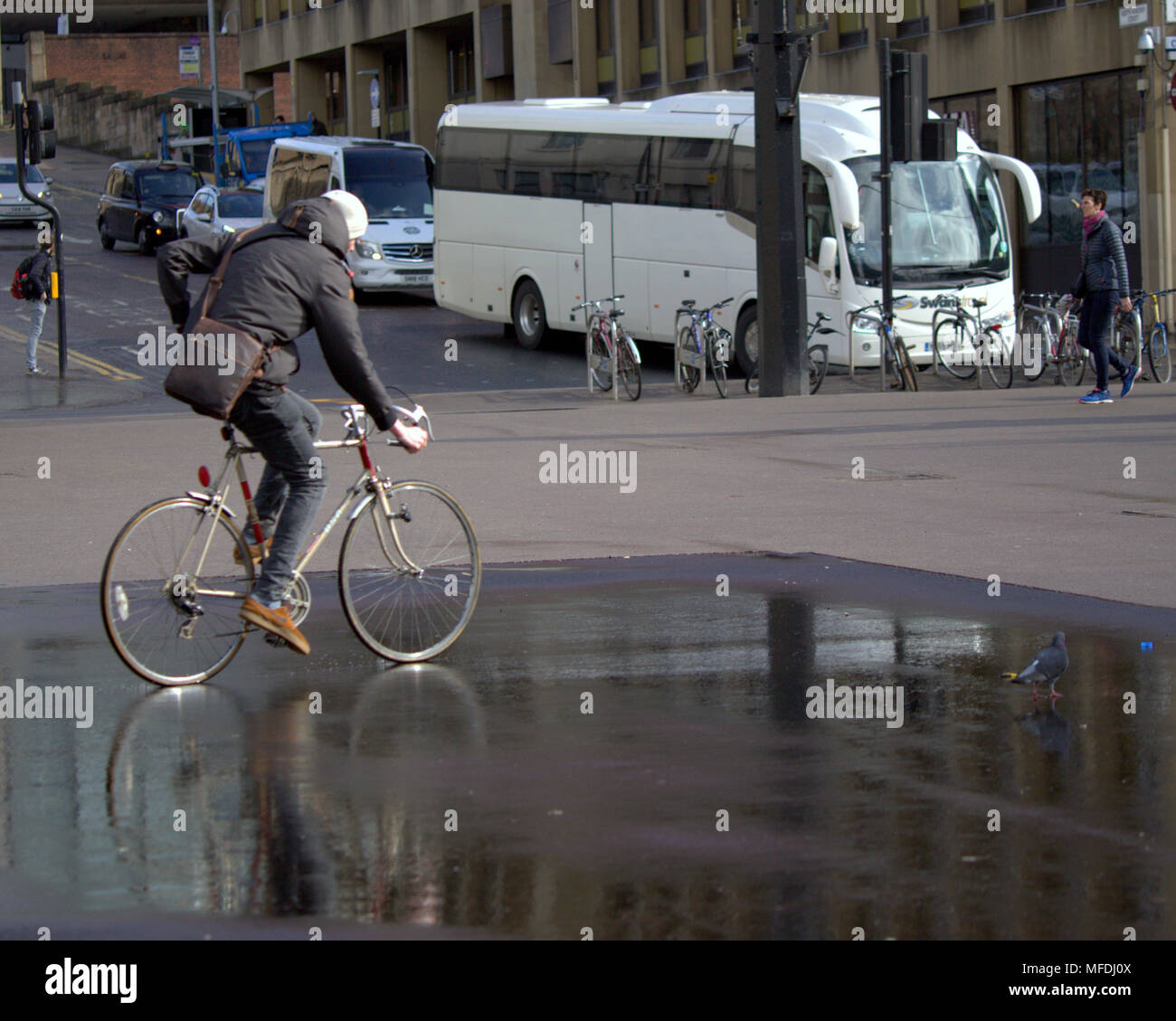 Glasgow, Scotland, UK 25th April. UK Weather: young man cycles on bike reflection in puddle with pigeon white tourist bus George Square locals and tourists inn  Sunshine and showers as the locals and tourists enjoy the beginning of summer. Gerard Ferry/Alamy news - Stock Image