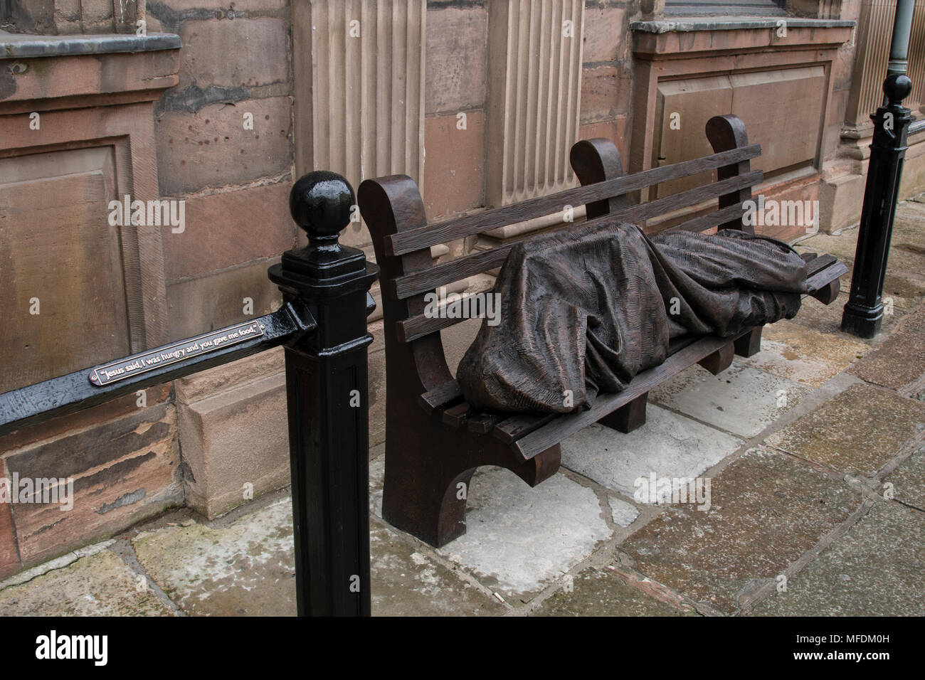 St. Annes Sq, Manchester, UK. 25th. April 2018: Homeless Jesus sculpture in St. Annes Square Manchester - a social comment on the homeless problem in the city. Homeless Jesus, also known as Jesus the Homeless, is the work of a Canadian sculptor and devout Catholic, Timothy Schmalz, whose original casting of Jesus on a park bench was installed in Toronto. Further casts have been made from the mould and have appeared in several cities around the world including the Papal Offices in Rome.. Credit: Dave Ellison/Alamy Live News - Stock Image