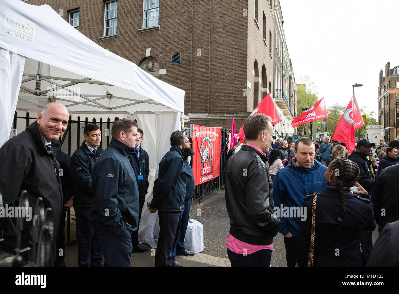 London, UK. 25th April, 2018. University of London security guards observe Independent Workers Union of Great Britain (IWGB) members protesting outside University of London Senate House in solidarity with workers employed by outsourcing companies contracted to the university currently striking to demand equal terms and conditions with those directly employed by the university. Cleaners, porters, security officers, receptionists, gardeners, post room staff and audiovisual staff have joined the strike after a near unanimous vote for industrial action. Credit: Mark Kerrison/Alamy Live News Stock Photo