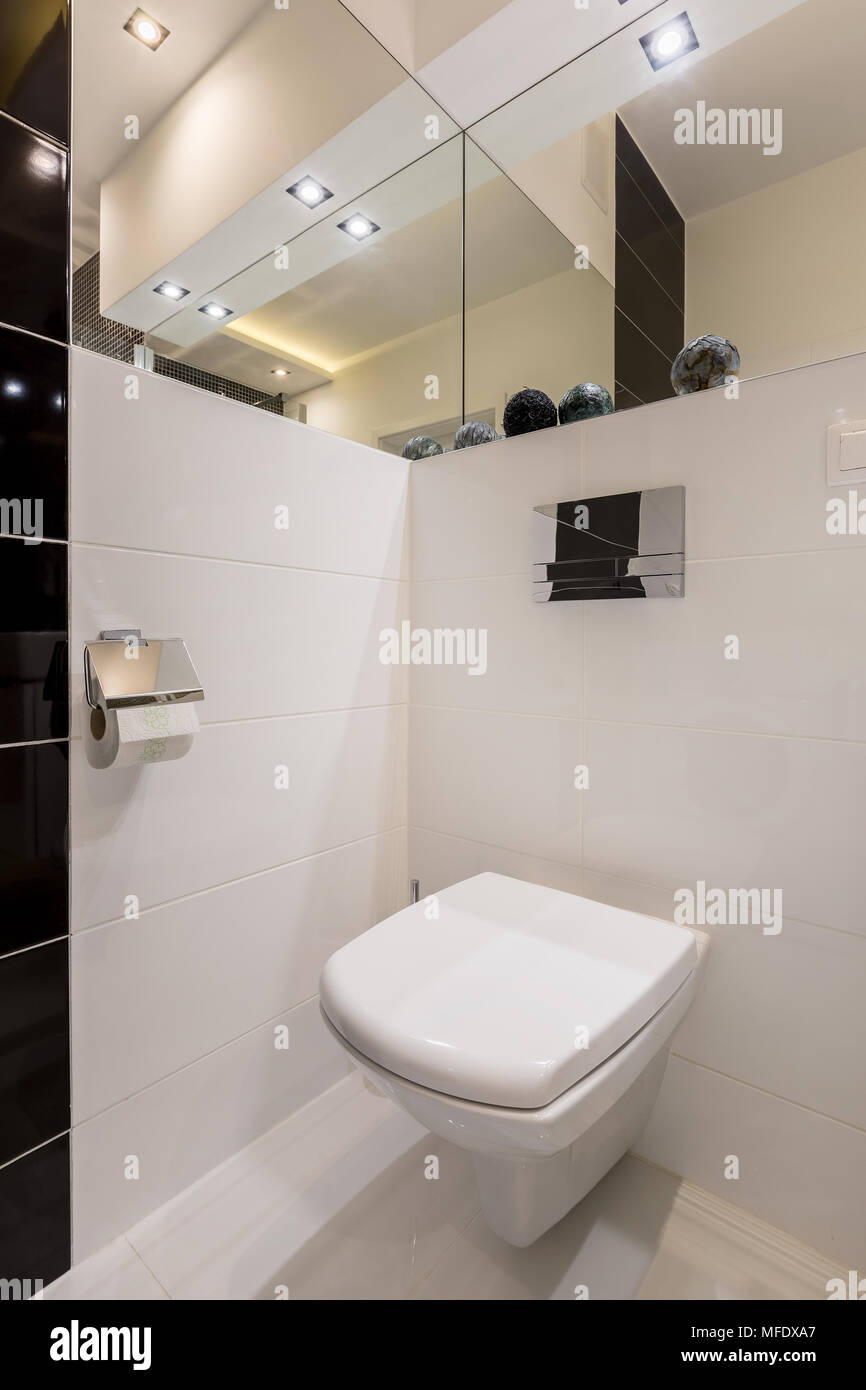 White toilet in modern bathroom with mirrors and led lamps - Stock Image