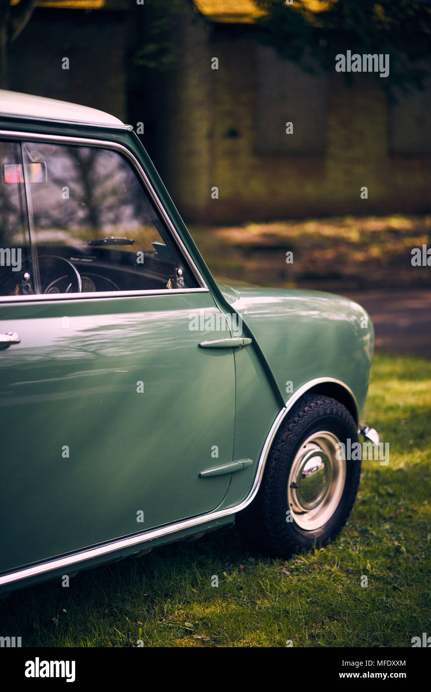 Portrait shot of a Green Mini Cooper in an Industrial setting - Stock Image