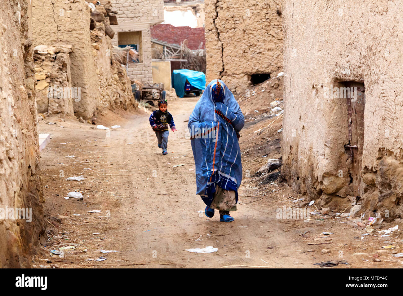 A woman in a burqa walking down a street of the old city of Siwa, Egypt - Stock Image