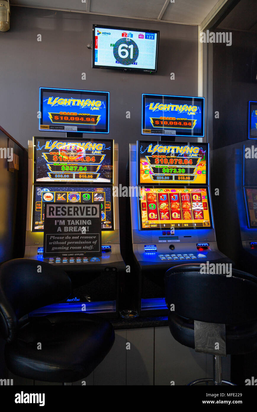 two poker slot machines at glen innes rsl club, one with reserve sign and Kino display on wall above - Stock Image