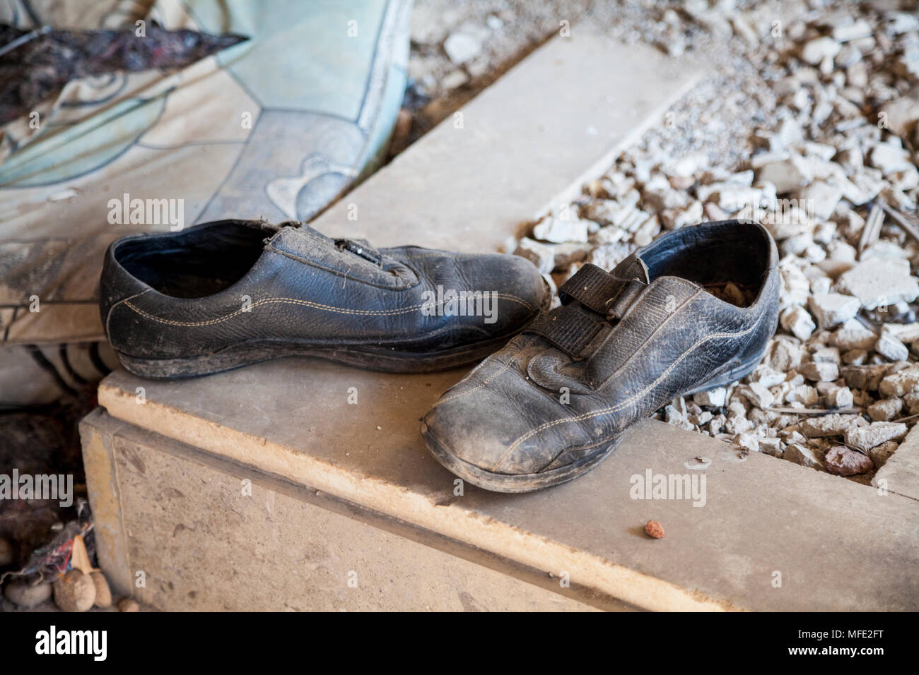 Close up of some shoes in an abandoned, bombed out building due to the Bosnian War in Mostar, Bosnia and Herzegovina - Stock Image