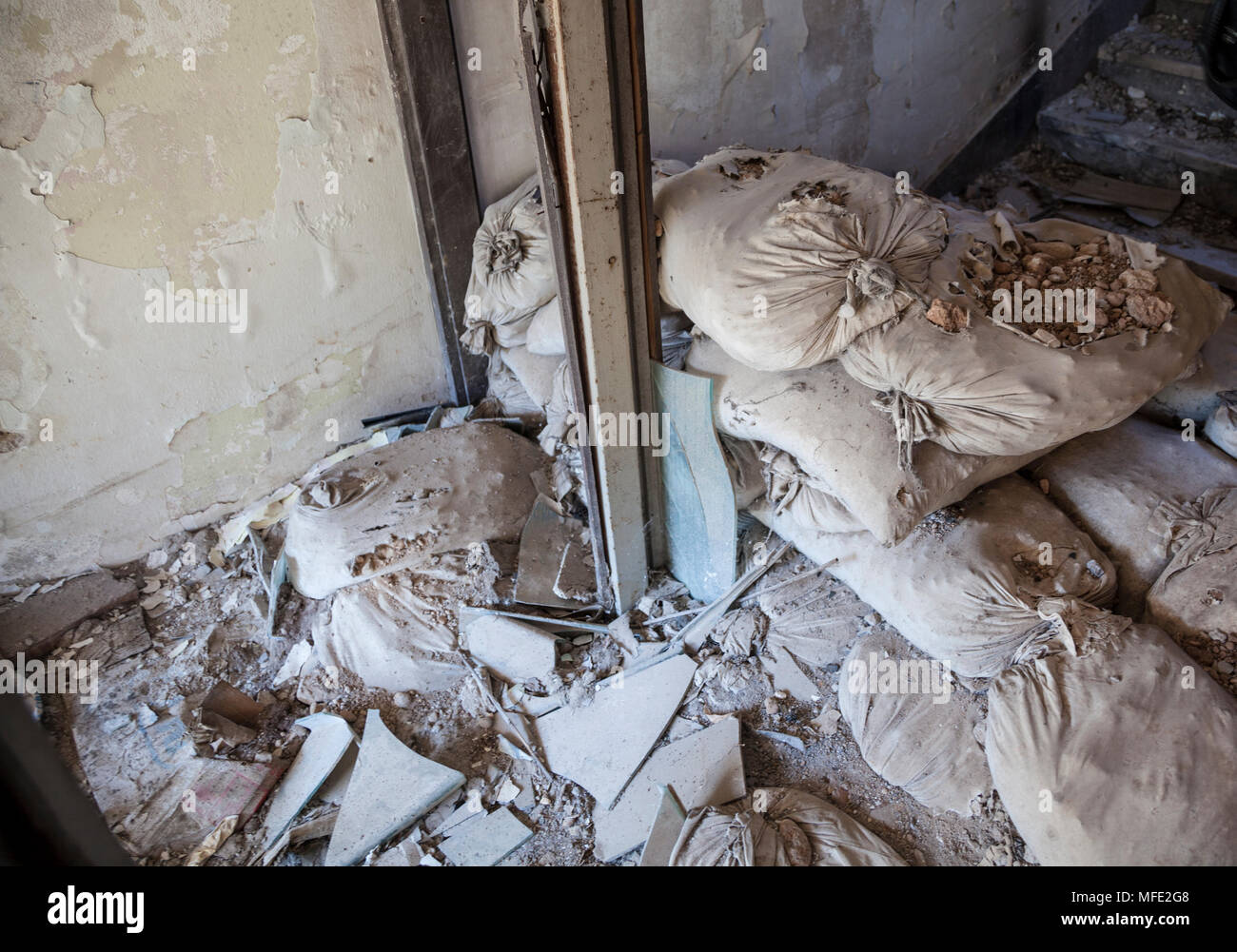Sand bags and rubbled from inside a bombed out building from Bosnian War in Mostar, Bosnia and Herzegovina - Stock Image